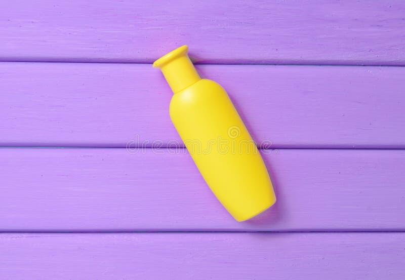 Uma garrafa amarela do champô em uma tabela de madeira roxa fotos de stock royalty free