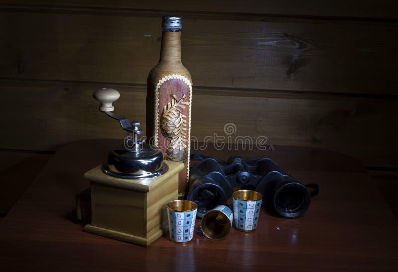 Uma garrafa coberta pela casca de vidoeiro, pelo moinho de café e pelo metal do ouro três imagens de stock royalty free