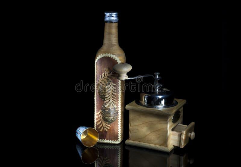 Uma garrafa coberta pela casca de vidoeiro, um moinho de café e um ouro metal g foto de stock
