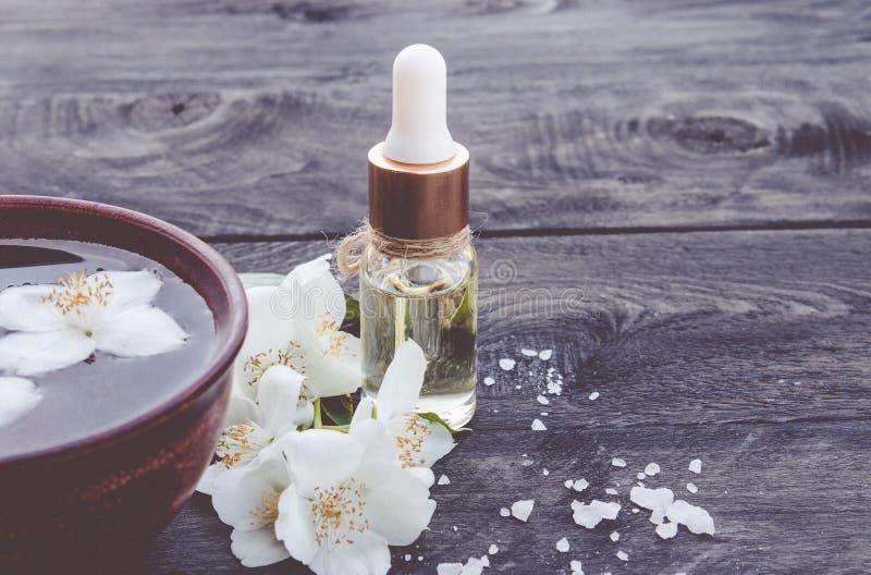 Uma garrafa com cosmético, óleo de jasmim aromático da massagem imagem de stock royalty free