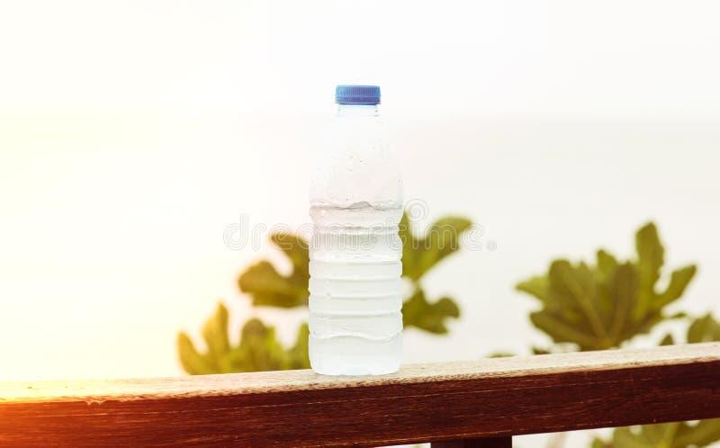 Uma garrafa da água potável limpa em um fundo natural com uma luz, o conceito de uma refeição saudável foto de stock