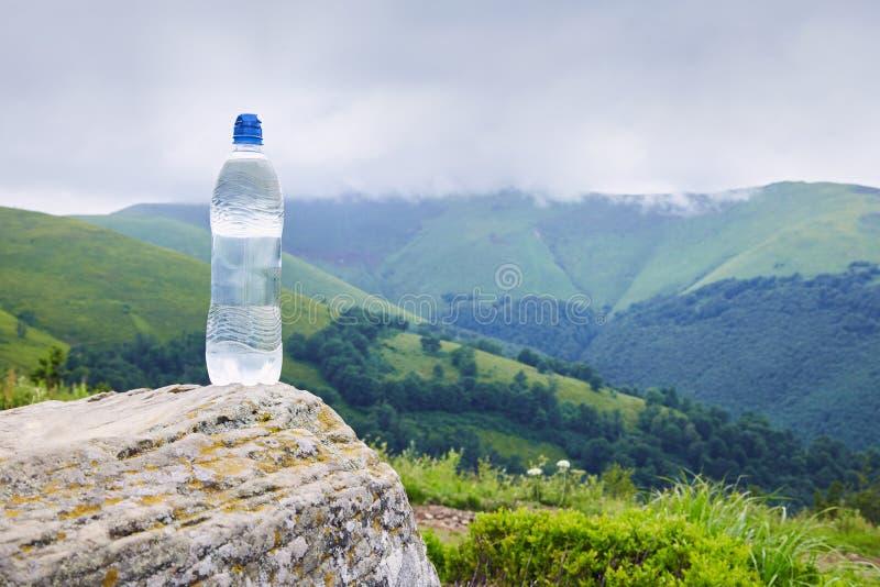 Uma garrafa da água potável pura na garrafa plástica na montanha fotos de stock