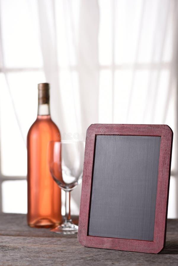 Uma garrafa de cora vinho com uma placa vazia do menu fotos de stock