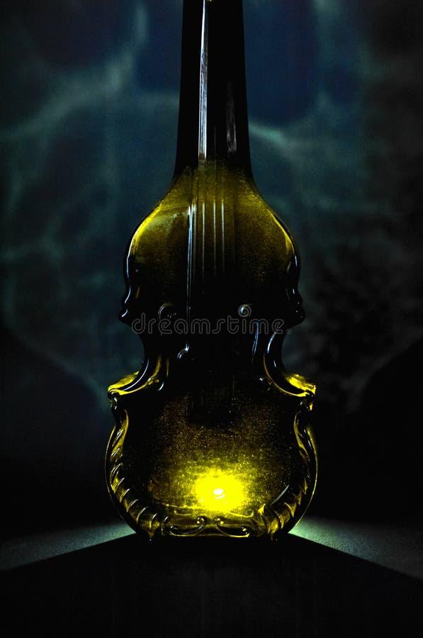 Uma garrafa de vidro luxuoso do conhaque, um formulário de um violino, com imagem de stock royalty free