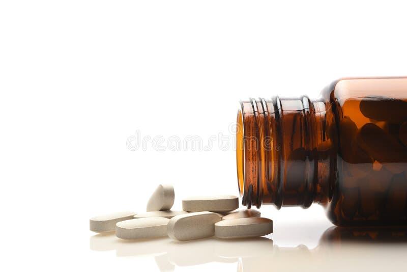Uma garrafa de vidro marrom da prescrição enchida com as vitaminas ou suplementos que derramam no tampo da mesa fotografia de stock royalty free