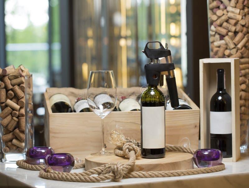 Uma garrafa de vinho com um corkscrew e um vidro vazio em uma prancha de madeira, um interior do restaurante, no fundo da fotos de stock royalty free