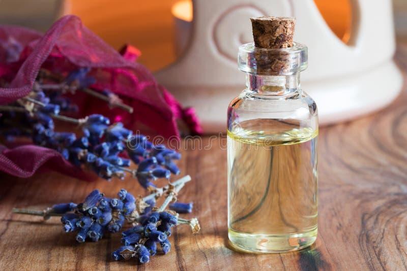 Uma garrafa do óleo essencial da alfazema em uma tabela de madeira imagem de stock royalty free