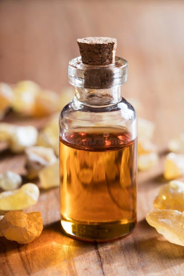 Uma garrafa do óleo essencial do incenso com resina do incenso imagens de stock royalty free