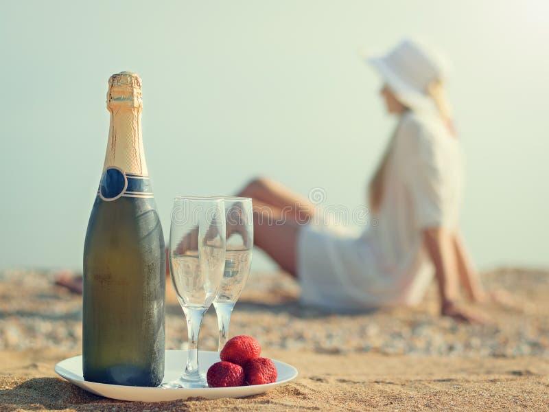 Uma garrafa do champanhe, dos vidros, das morangos, e da mulher na areia imagem de stock