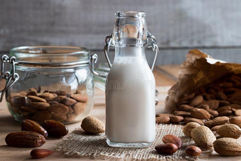 Uma garrafa do leite da amêndoa com as amêndoas inteiras e descascadas imagens de stock royalty free
