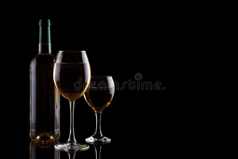 Uma garrafa do vinho branco e dos dois vidros com vinho branco em um fundo escuro imagem de stock royalty free