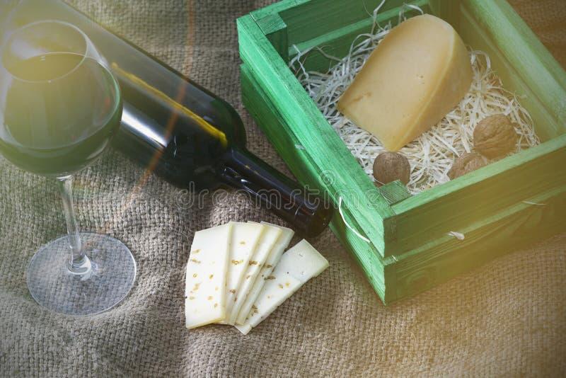 Uma garrafa do vinho tinto com um vidro e uma parte de queijo foto de stock