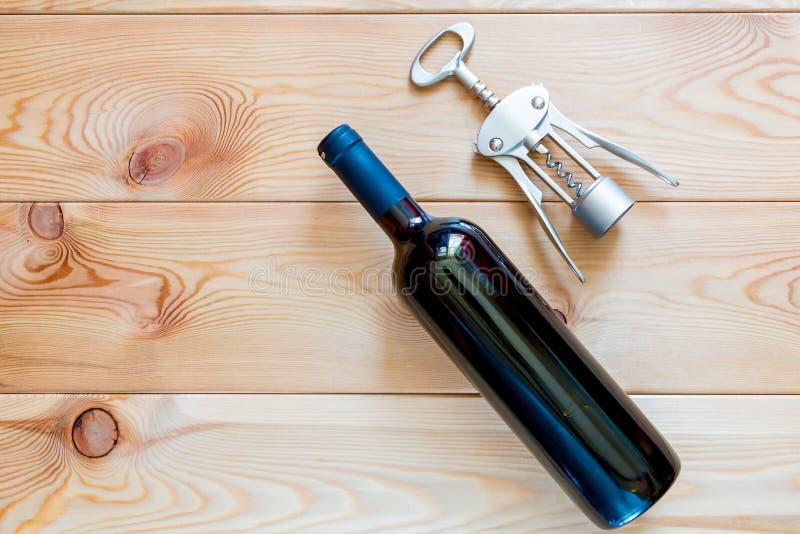 uma garrafa do vinho tinto e de um corkscrew na opinião superior c de placas de madeira foto de stock