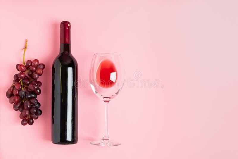 Uma garrafa do vinho um o vidro vazio de um grupo de uvas em um fundo cor-de-rosa delicado minimalism Disposi??o lisa da vista su imagens de stock royalty free