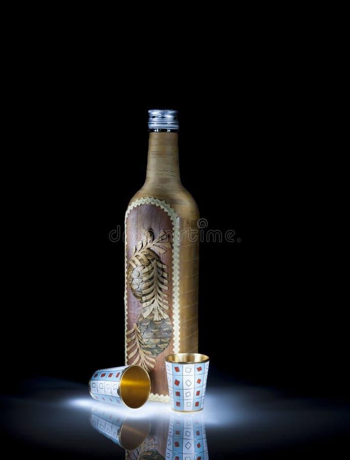 Uma garrafa e dois vidros do metal do ouro fotos de stock
