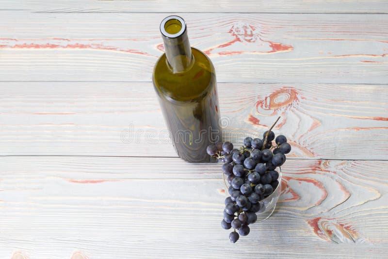 Uma garrafa e um vidro nele são um ramo de uvas escuras, contra um fundo cinzento em um fundo de madeira foto de stock