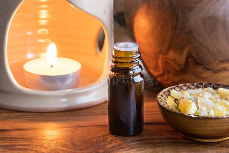 Uma garrafa escura do óleo essencial do incenso com incenso com referência a imagem de stock