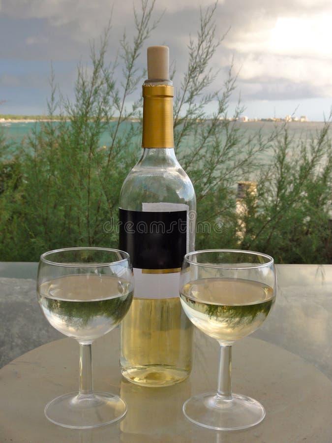 Uma garrafa meio vazia do vinho branco e de dois encheu os vidros, exteriores em um dia de verão, com o mar no fundo fotografia de stock