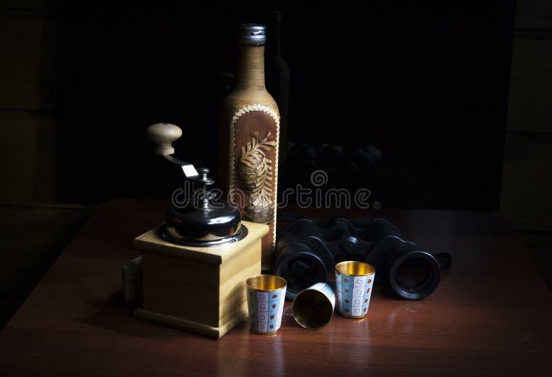 Uma garrafa, moinho de café, binóculos e três vidros do metal do ouro foto de stock