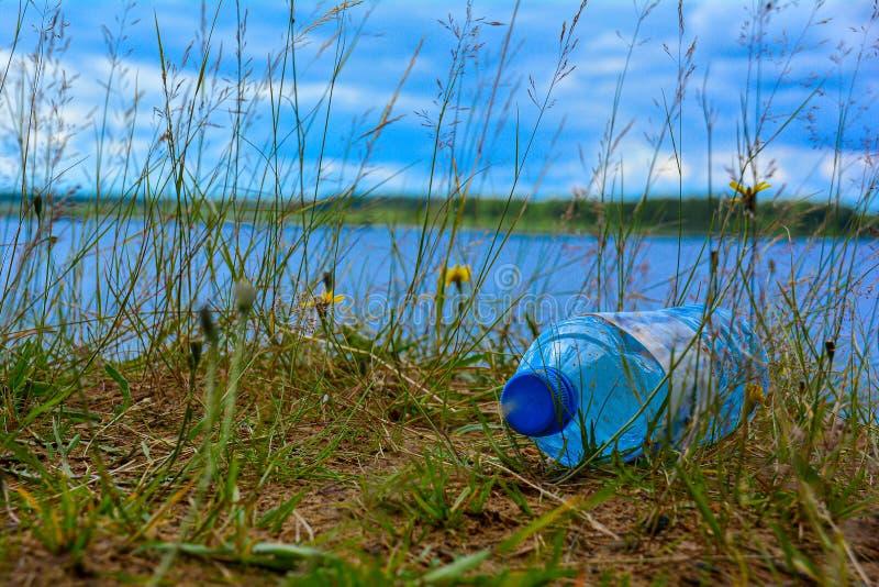 Uma garrafa plástica velha encontra-se no banco de rio na grama Desastre do lixo do conceito de Eco da poluição ambiental O probl foto de stock