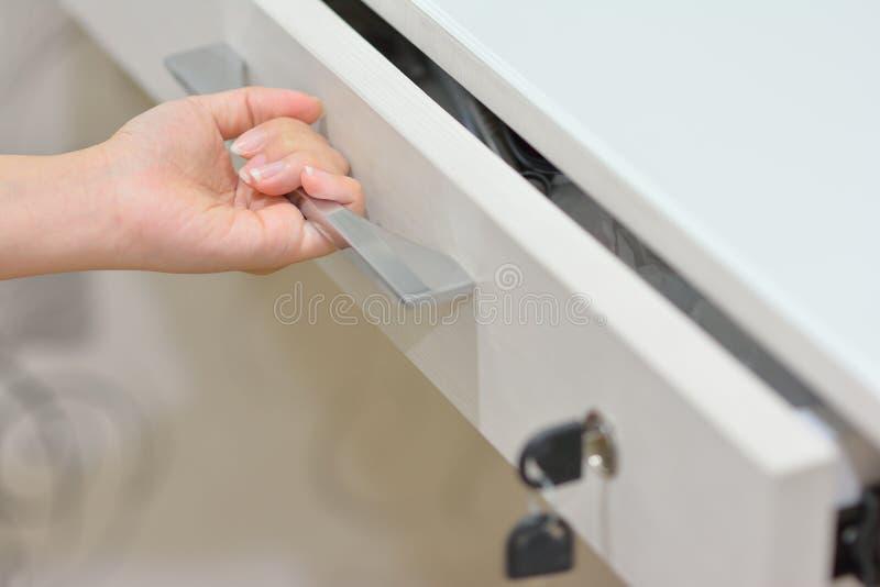 Uma gaveta branca de abertura da mão imagem de stock