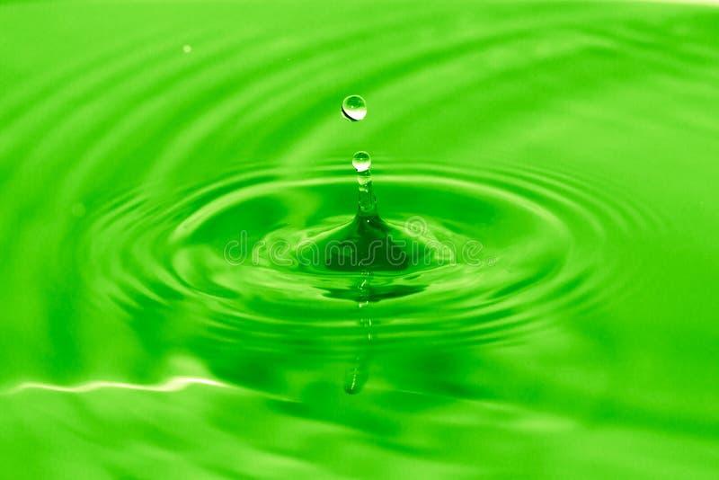 Uma gota da água cai na água verde foto de stock