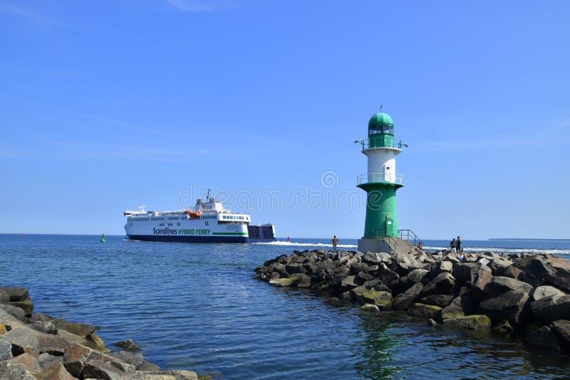 Uma grande balsa está vista sair do porto de Warnemunde, Alemanha enquanto passa um farol verde pequeno nesta data imagens de stock royalty free