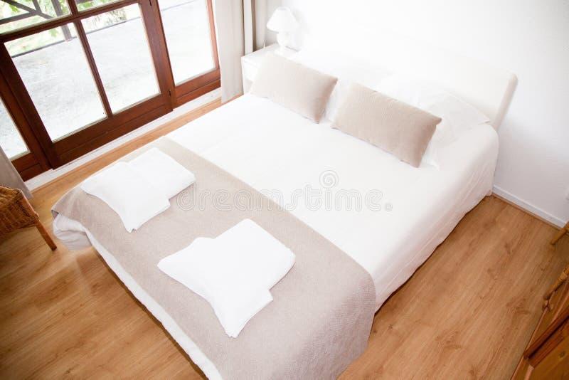 Uma grande cama muito bonita em um quarto fotografia de stock