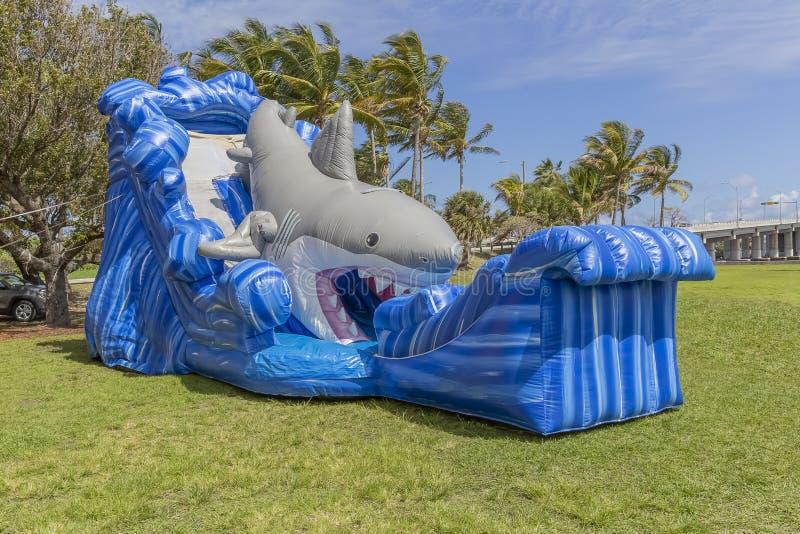 Uma grande casa inteiramente inflada do salto do tubarão com ondas enormes está alta no parque fotografia de stock