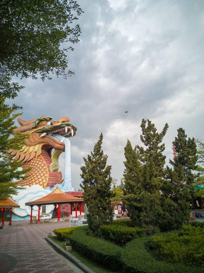 Uma grande construção do dragão no jardim quando o céu estiver próximo chover fotografia de stock royalty free