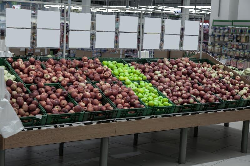 Uma grande cremalheira com as cestas com tipos diferentes de maçãs no departamento do fruto do shopping Alimentos frescos e saudá fotos de stock royalty free