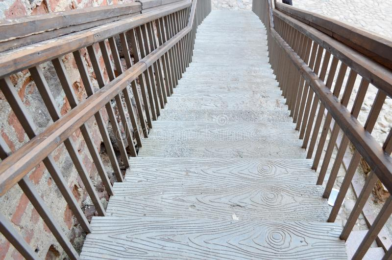Uma grande escadaria marrom de madeira que conduz para baixo com etapas e trilhos O fundo imagem de stock royalty free