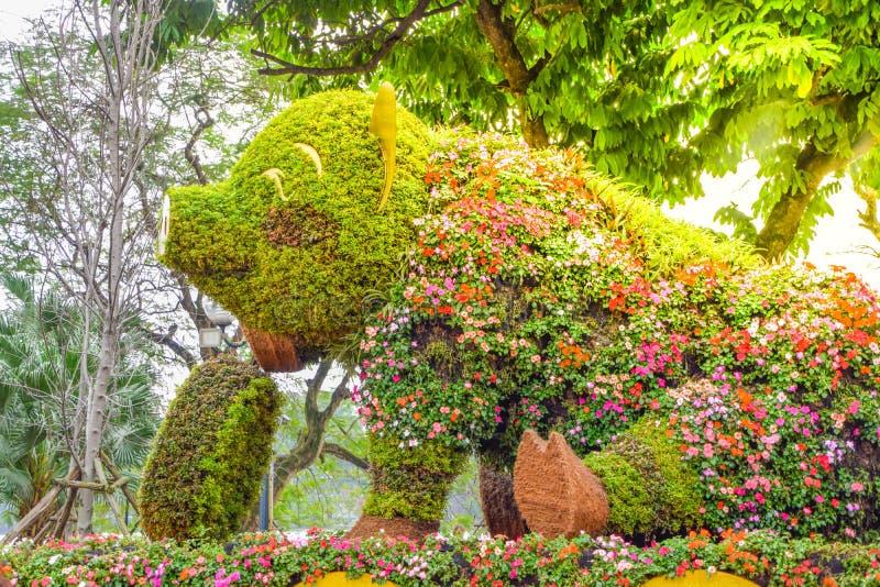 Uma grande estátua do porco do assento e do sorriso decorada com flores bonitas e as flores coloridas em um parque em Hanoi, Viet fotografia de stock