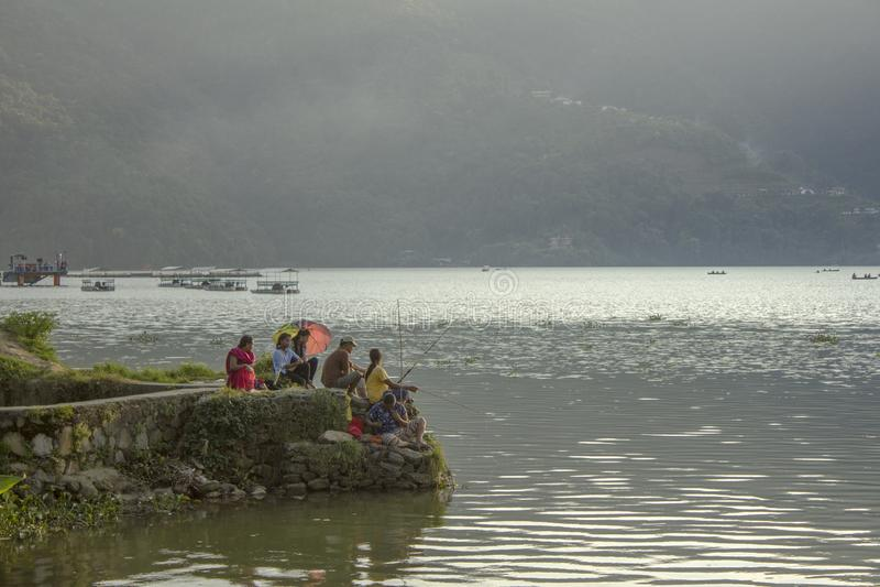 Uma grande família senta-se pelo lago com varas de pesca e um guarda-chuva na perspectiva do verde fotos de stock royalty free