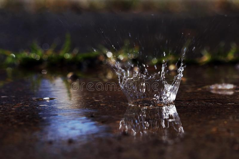 Uma grande gota da chuva bate a terra fotos de stock