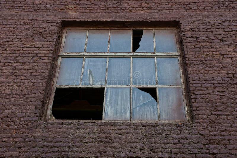 Uma grande janela quebrada velha em uma parede de tijolo marrom fotografia de stock royalty free