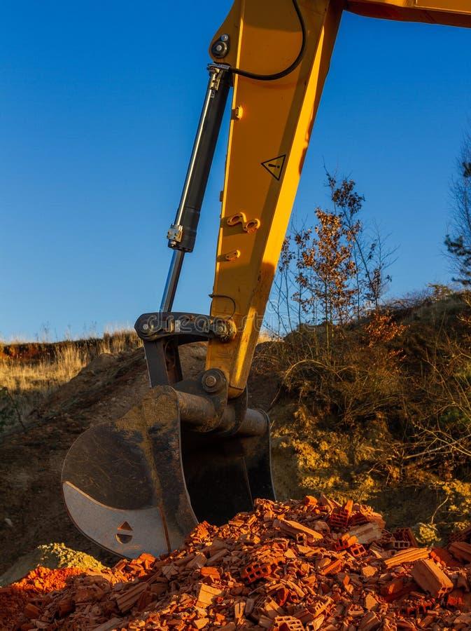 Uma grande máquina escavadora amarela em um canteiro de obras foto de stock royalty free