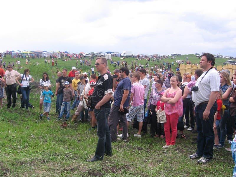 Uma grande multidão de povos dos espectadores recolheu a observação do espetáculo no prado no verão de Kolyvan 2013 fotografia de stock