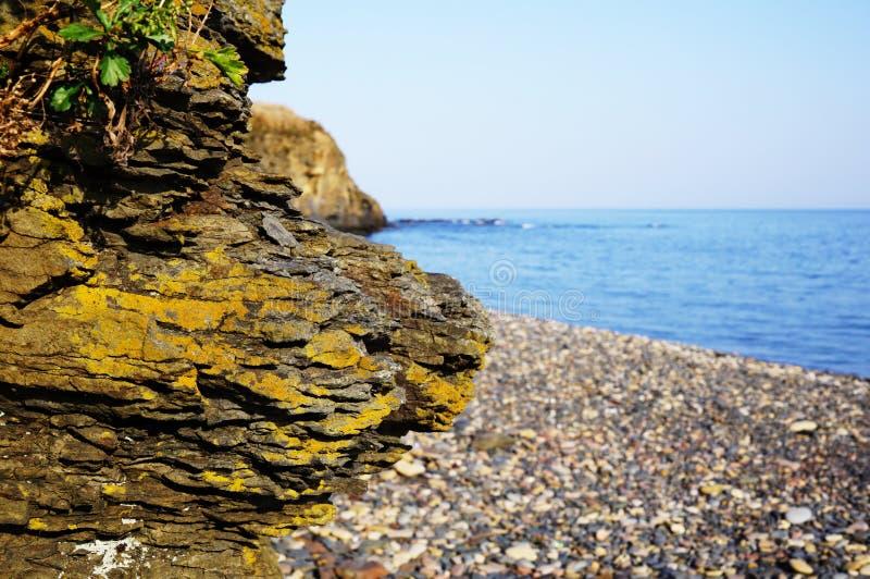 Uma grande parte do fim da rocha acima contra o mar fotografia de stock