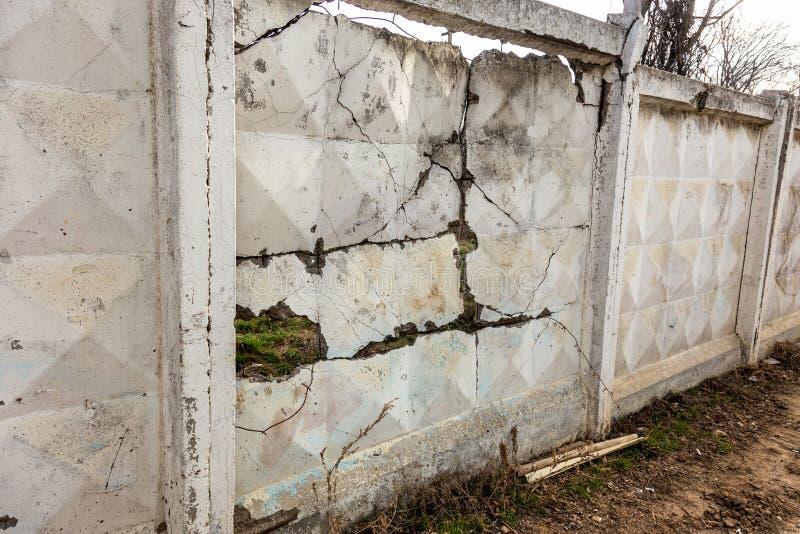 Uma grande quebra na parede de pedra velha Fundo de uma parede de tijolo de pedra de uma construção com uma quebra perigosa diret imagens de stock royalty free
