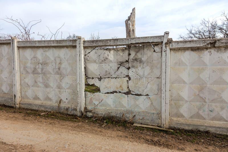 Uma grande quebra na parede de pedra velha Fundo de uma parede de tijolo de pedra de uma construção com uma quebra perigosa diret foto de stock royalty free