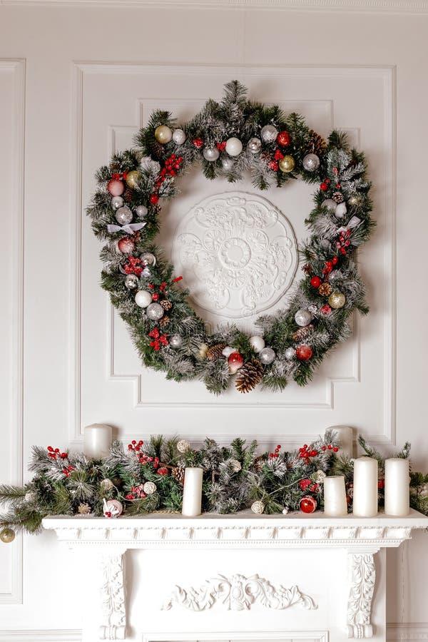 Uma grinalda tradicional, brilhante do Natal que pendura sobre a chaminé, em uma parede branca Conceito do Natal, ano novo interi foto de stock royalty free