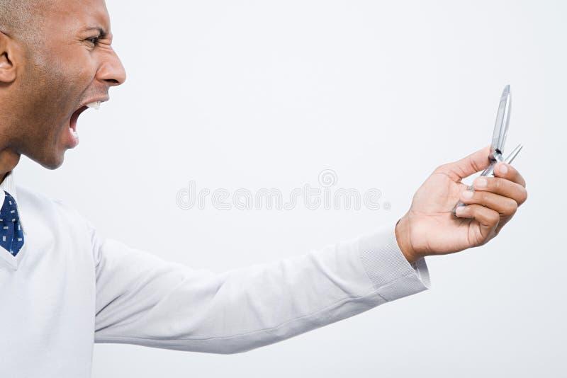 Uma gritaria do homem em um telefone celular foto de stock royalty free