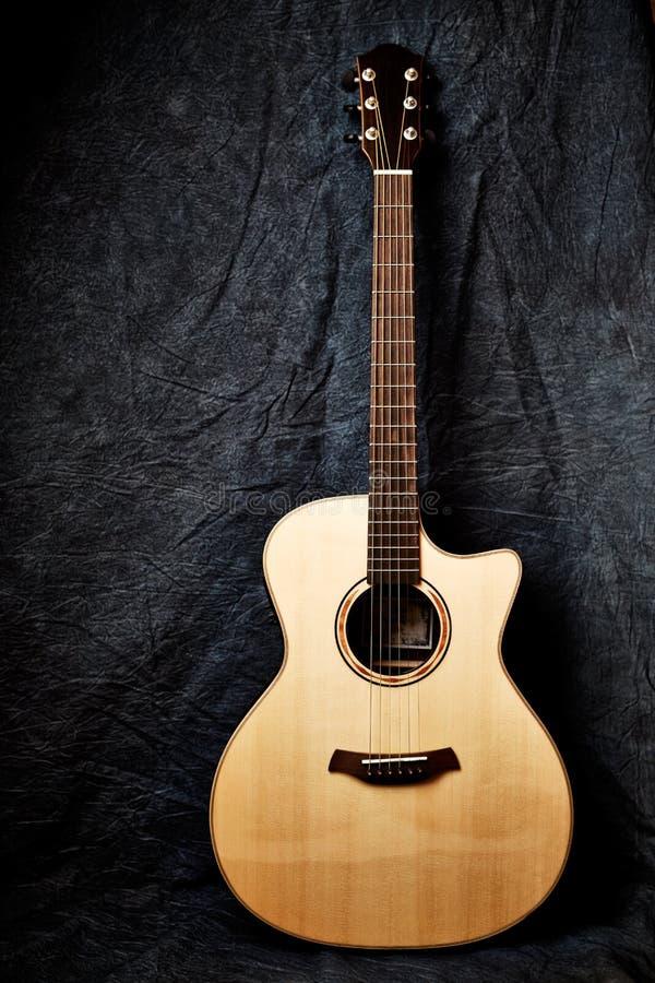 Uma guitarra acústica no fundo escuro de pano foto de stock