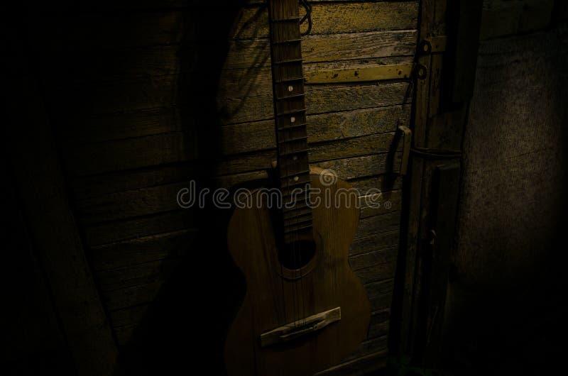 Uma guitarra ac?stica de madeira est? de encontro a uma parede textured grunge A sala é escura com um projetor para seu copyspace imagens de stock