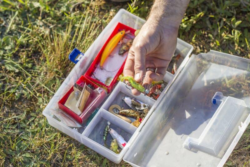 Uma haste do ` s do pescador escolhe uma isca de giro da caixa fotografia de stock