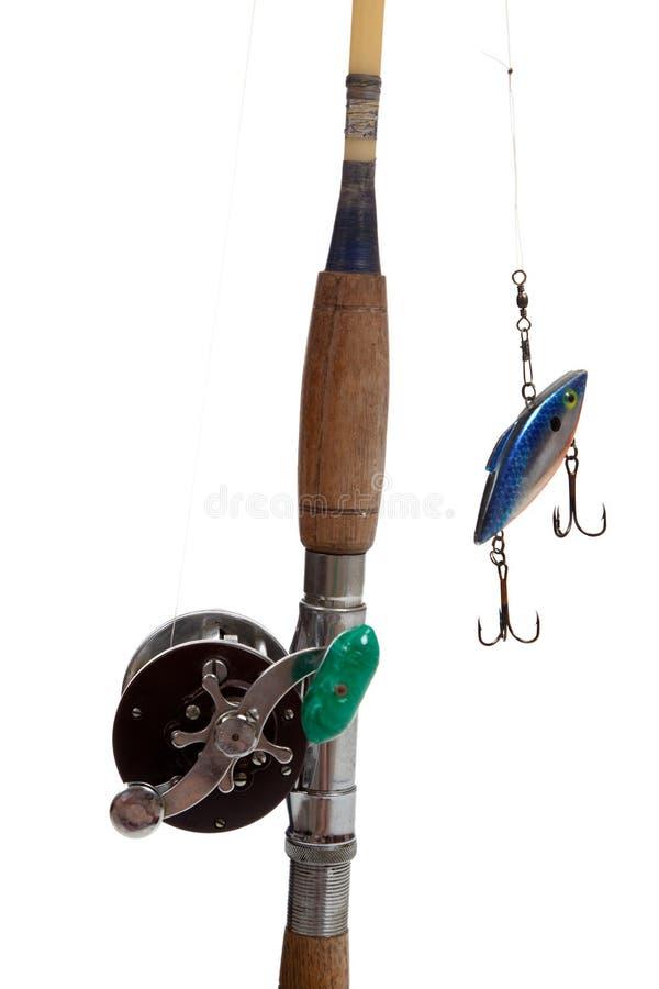 Uma haste, um carretel e uma atração de pesca em um fundo branco imagens de stock royalty free