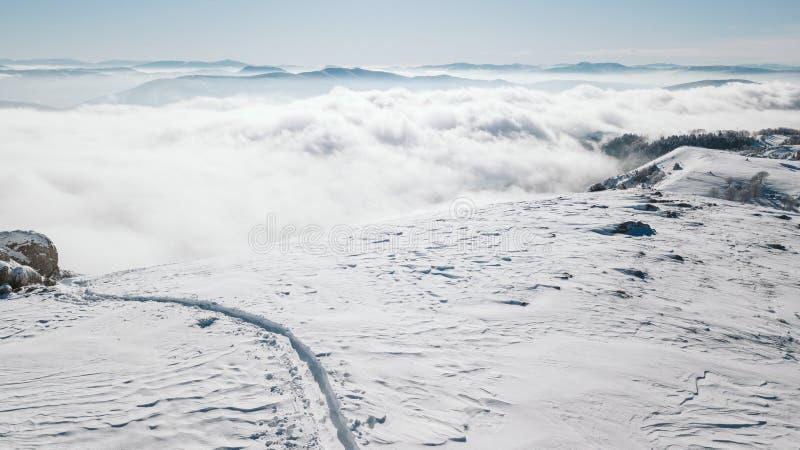Uma ideia da inclinação nevado no vale coberto com a névoa imagens de stock