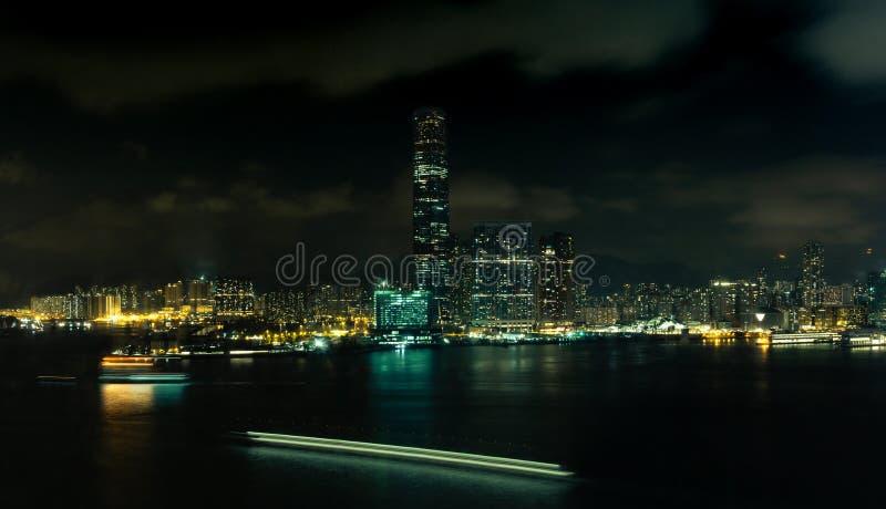 Uma ideia da noite da margem de Kowloon na noite com as fugas da luz do barco - 2 foto de stock royalty free