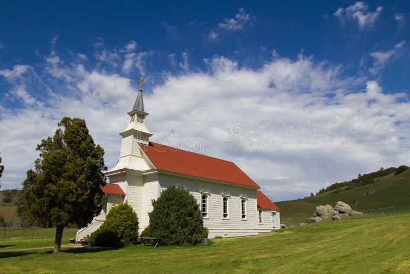 Ângulo lateral de uma igreja branca pequena com um telhado vermelho em Califórnia do norte com os céus azuis desiguais fotografia de stock royalty free